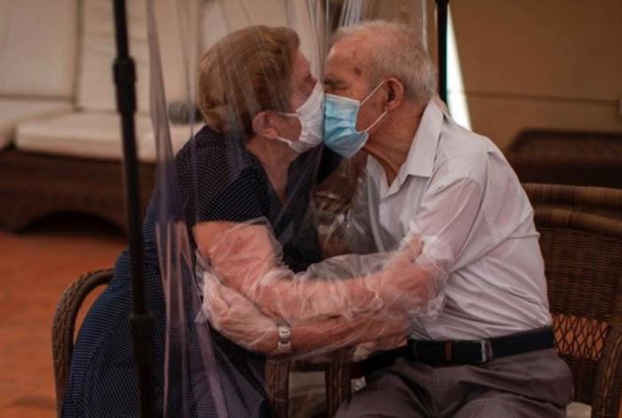 Amor em tempos de pandemia: casal de idosos se beija com cortina de plástico